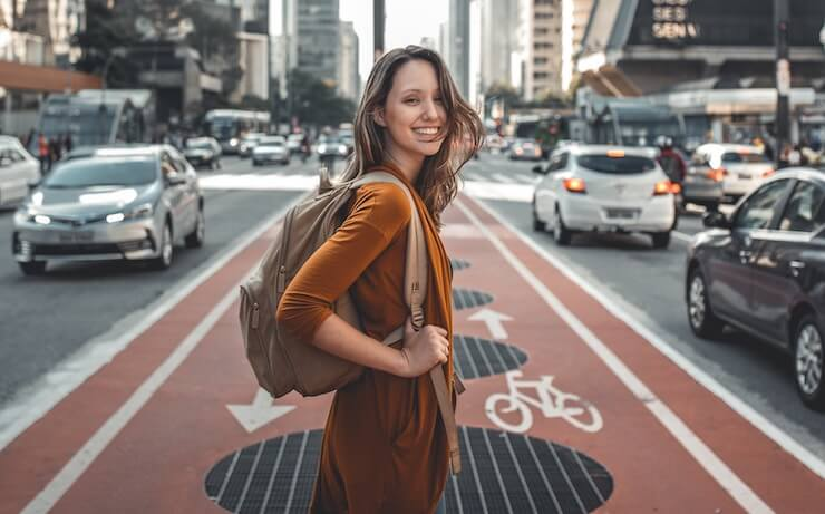 Woman excited about traveling in a city holding a backpack