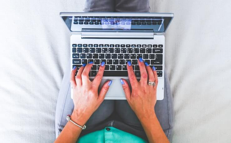 woman relaxing while writing reviews to make money in bed