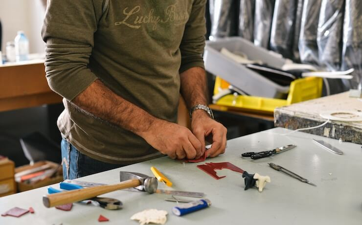Man wearing a green long sleeve shirt working on a craft at his home workshop