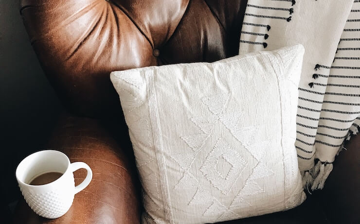 Cozy couch with cup of coffee at home with white pillow
