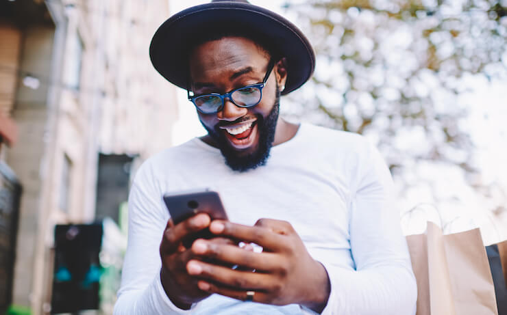 man surprised that his hobby could make him money looking at his phone while wearing a white long sleeved shirt